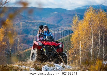 Women Riding On Atv In Winter Clothing On Snowy Hills On The Background Of Mighty Mountains And Tree