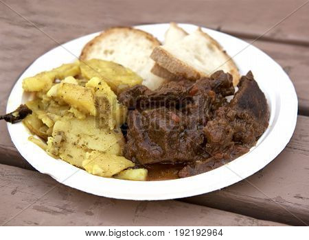 Stewed horse meat with potatoes and bread.Traditional maltese cuisine. Horse meat on white plastic plate served with maltese source, potatoes, vegetables. Feast in Qormi city, Malta open kitchen