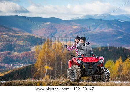 Happy Couple On Red Quad Bike Riding In The Mountains. Young Man Driving The Atv, Girlfriend Pointin