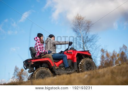 Bottom View Couple On The Red Atv Quad Bike Against Blue Sky With Blurred Background Nature. Woman H