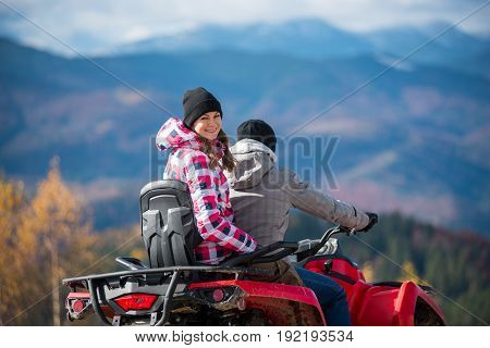 Close-up Of Guy Manages Atv, Girl Sitting Behind Him And Turned Around Looking At The Camera On Blur