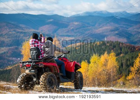 Man Manages Quadbike, Girlfriend Sitting Behind Him Makes Photo Of Beautiful Landscape Mountains And
