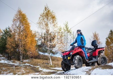 Happy Woman In Blue Winter Clothes Riding On A Red Quadbike Atv On Snow-covered Hill Against Autumn