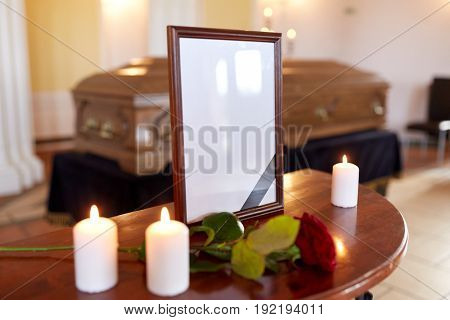 funeral and mourning concept - photo frame with black ribbon, burning candles and coffin at church