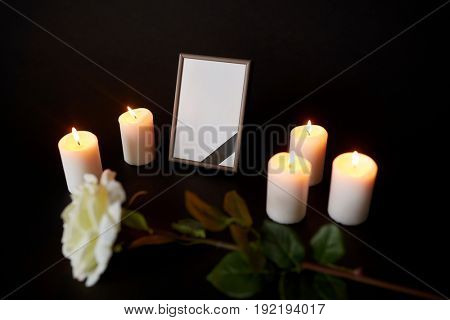 funeral and mourning concept - photo frame with black ribbon, flower and burning candles in darkness