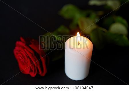 funeral and mourning concept - red rose and burning candle over black background
