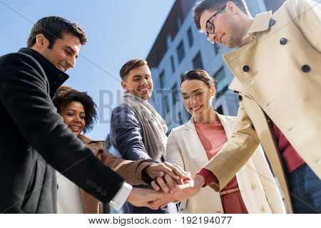 business, education and corporate concept - international group of people holding hands together on city street