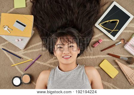 Directly above view of pretty Asian woman lying on floor and posing for photography, digital tablet, notebooks and cosmetics scattered everywhere