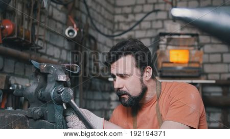 Blacksmith bends metal knife with gripe in workshop forge, portrait, telephoto