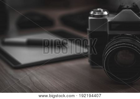 Still life of photographer desk in home office interior. Professional photo media working equipment camera body lenses monitor and tablet.