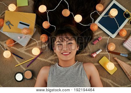 Attractive Vietnamese woman looking at camera with toothy smile while lying on floor, directly above view