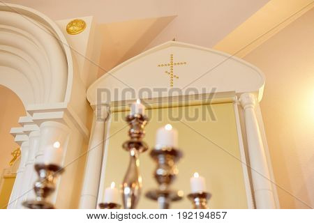 religion and christianity concept - candles burning in orthodox church
