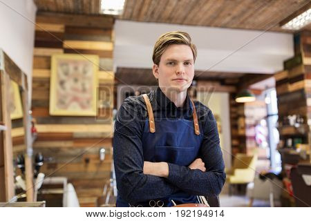 profession, grooming and people concept - male stylist or hairdresser in apron at hair salon or barbershop