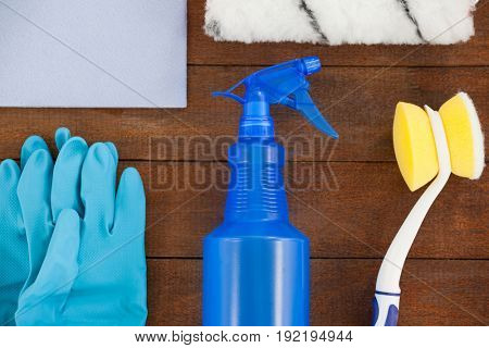 Close-up of various cleaning equipment arranged on wooden floor