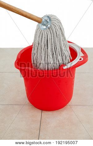 Mop in red bucket on tile floor against white wall