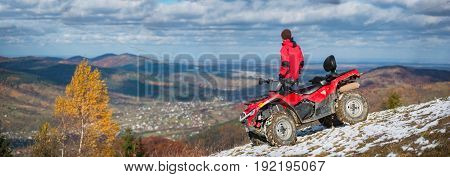 Panorama Picture. Off-road Vehicle And Man Near Him On A Snowy Mountain Top Under The Blue Cloudy Sk