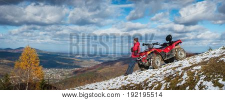 Panorama. Man Standing Near Atv Quad Bike, Looking Into The Distance On Snowy Mountain Top. On The B