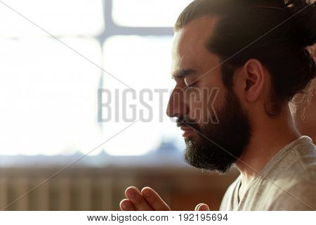 religion, faith and people concept - close up of man meditating at yoga studio