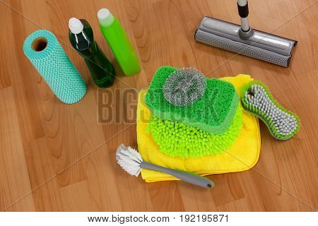 Close-up of various cleaning equipment on wooden floor