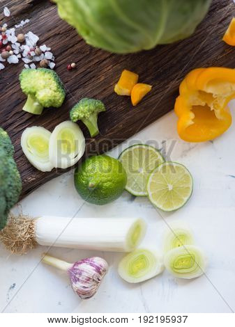 Chopped and sliced vegetables on wooden cutting board, view from above