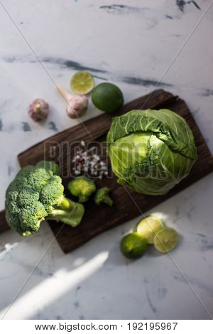 Cabbage and broccoli on wooden cutting board, view from above