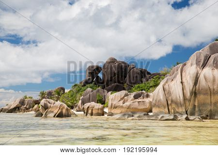 travel, landscape and nature concept - rocks on seychelles island beach in indian ocean