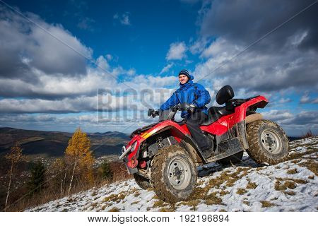 Smiling Male On The Quad Riding Down On The Snowy Slope On A Sunny Autumn Day. Beautiful Mountain La
