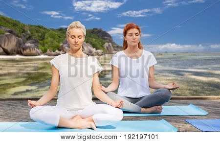 fitness, sport, yoga and people concept - women meditating in lotus pose outdoors
