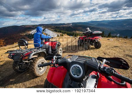 View from a quad bike with men driving an ATV in front on the top of mountain trail with perfect background mountains forests and sky with cumulus clouds in autumn