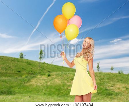 people, summer holidays and party concept - happy young woman or teen girl in pink dress with helium air balloons over blue sky and green field background