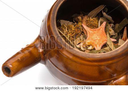 herbal in enamel pot on white background
