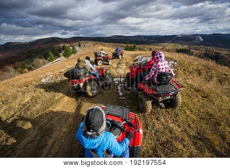 Top View Of A Group Of People Riding A Off-road Vehicles On A Mountain Road Under A Sky With Clouds