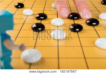 fingers placing piece of GO on board with a robot in front concept of human against robot