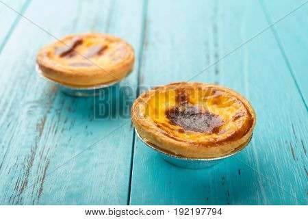 studio shoot of portuguese egg tarts on a wood background