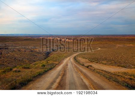 Desert dirt road to Coalmine Canyon near Page Arizona. Taking looking downhill of an 8% grade. The landscape is lit by golden light filtered through a smoky sky.