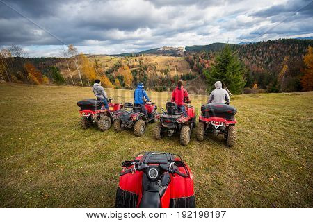 View From Quad Bike With Four Men At Atv In Front On The Top Of Hill. Beautiful Landscape Of Rolling