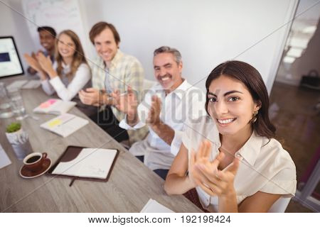 Portrait of smiling business people applauding during presentation in office
