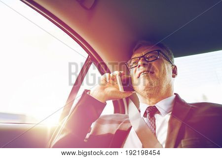 transport, business trip, technology and people concept - senior businessman calling on smartphone and driving on car back seat