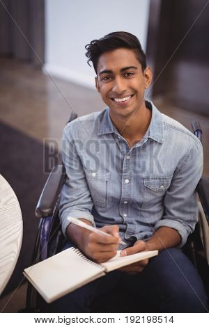 Portrait of smiling businessman writing in book while sitting on wheelchair