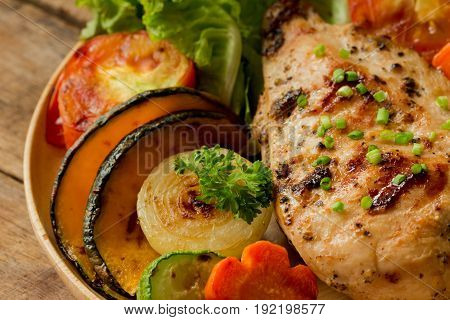 Homemade chicken breast barbecue on wood plate served with grilled vegetables. Delicious chicken barbecue and grilled vegetables for lunch or dinner. Roast chicken breast on rustic wood table. Piece of chicken barbecue or pork steak.