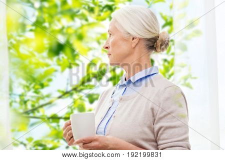 age, loneliness and people concept - lonely senior woman with cup of tea or coffee looking through window at home over window and green natural background