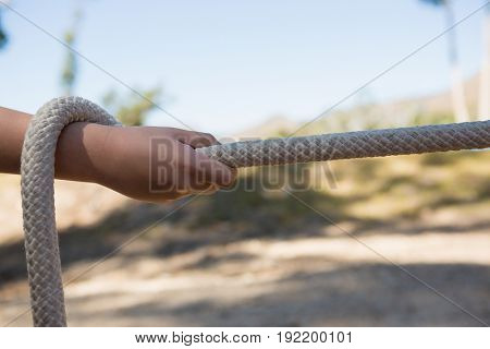 Hand of kid practicing tug of war during obstacle course in the boot camp