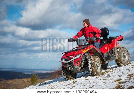 Happy Man Riding On Red Four Wheel Quad Bike On The Snowy Mountain Slope. Blue Sky With Clouds On Th