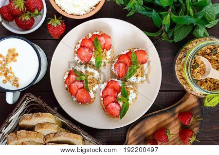 Mini sandwiches with cottage cheese fresh strawberries decorated with mint leaves on rye bread on a dark wooden background. Top view. Proper nutrition. Healthy food. Dietary menu.