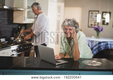Portrait of smiling senior woman using laptop while husband cooking in kitchen