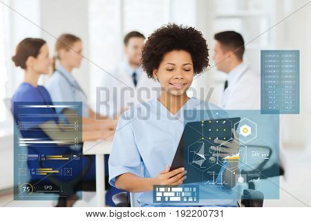 medicine, healthcare, technology and people concept - happy african american female doctor or nurse with clipboard over group of medics at hospital