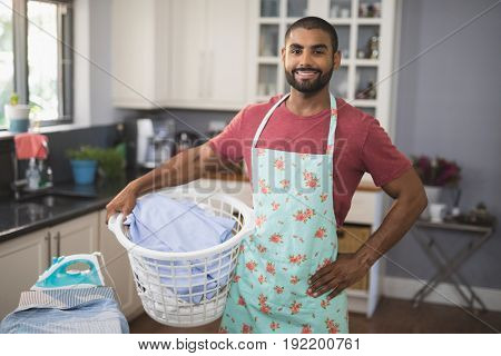 Portrait of smiling young man holding laundry basket by ironing board in kitchen at home
