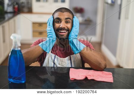 Portrait of surprised young man by marble counter in kitchen at home
