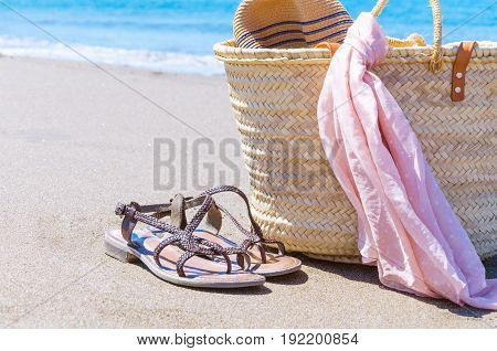 Beach accessories on coastline: beach straw bag, summer cute sandals and pareo. Holiday time, travel or vacation concept. Space for text.
