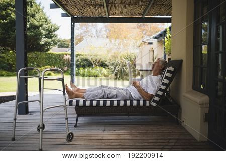 Walker by senior man resting on lounge chair at porch